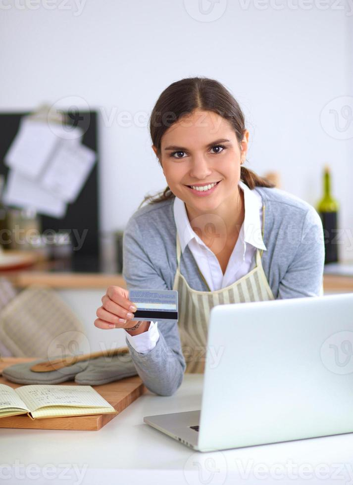 mulher sorridente compras online usando computador e cartão de crédito em foto
