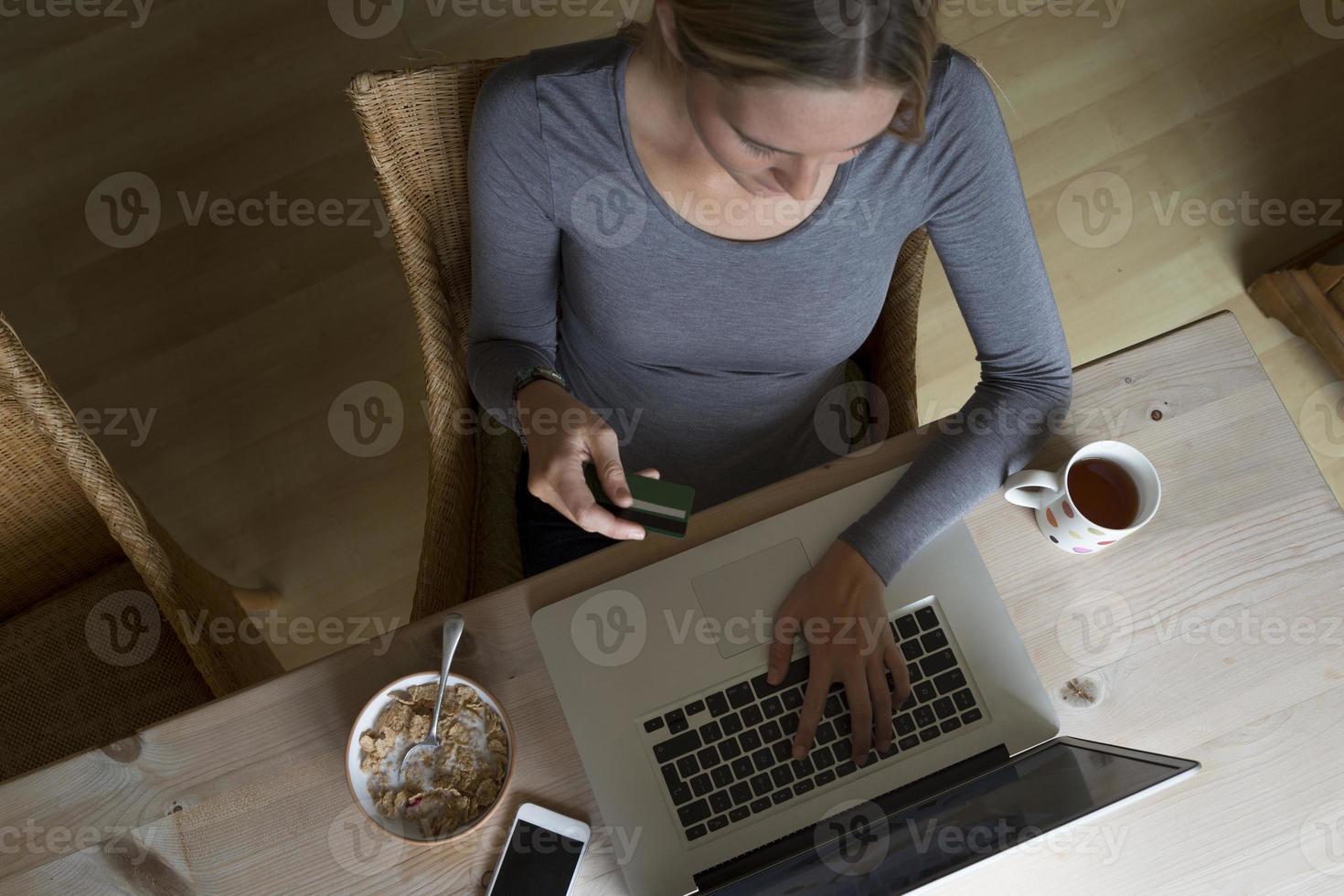 mulher usando o laptop para fazer um pagamento com cartão foto
