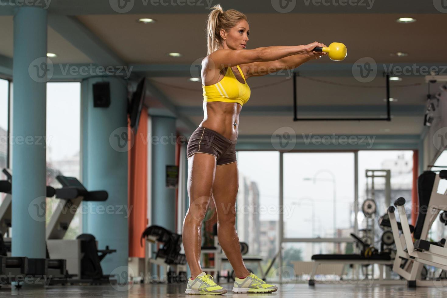 mulher de meia idade exercício com kettlebell foto