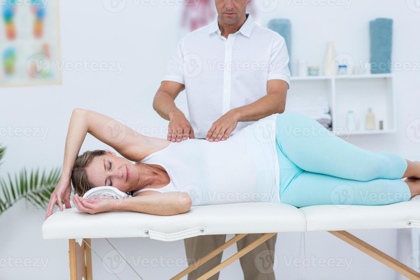 médico massageando seu paciente foto
