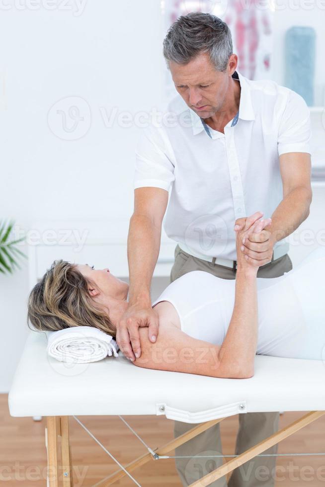 médico, dobrando o braço do paciente foto