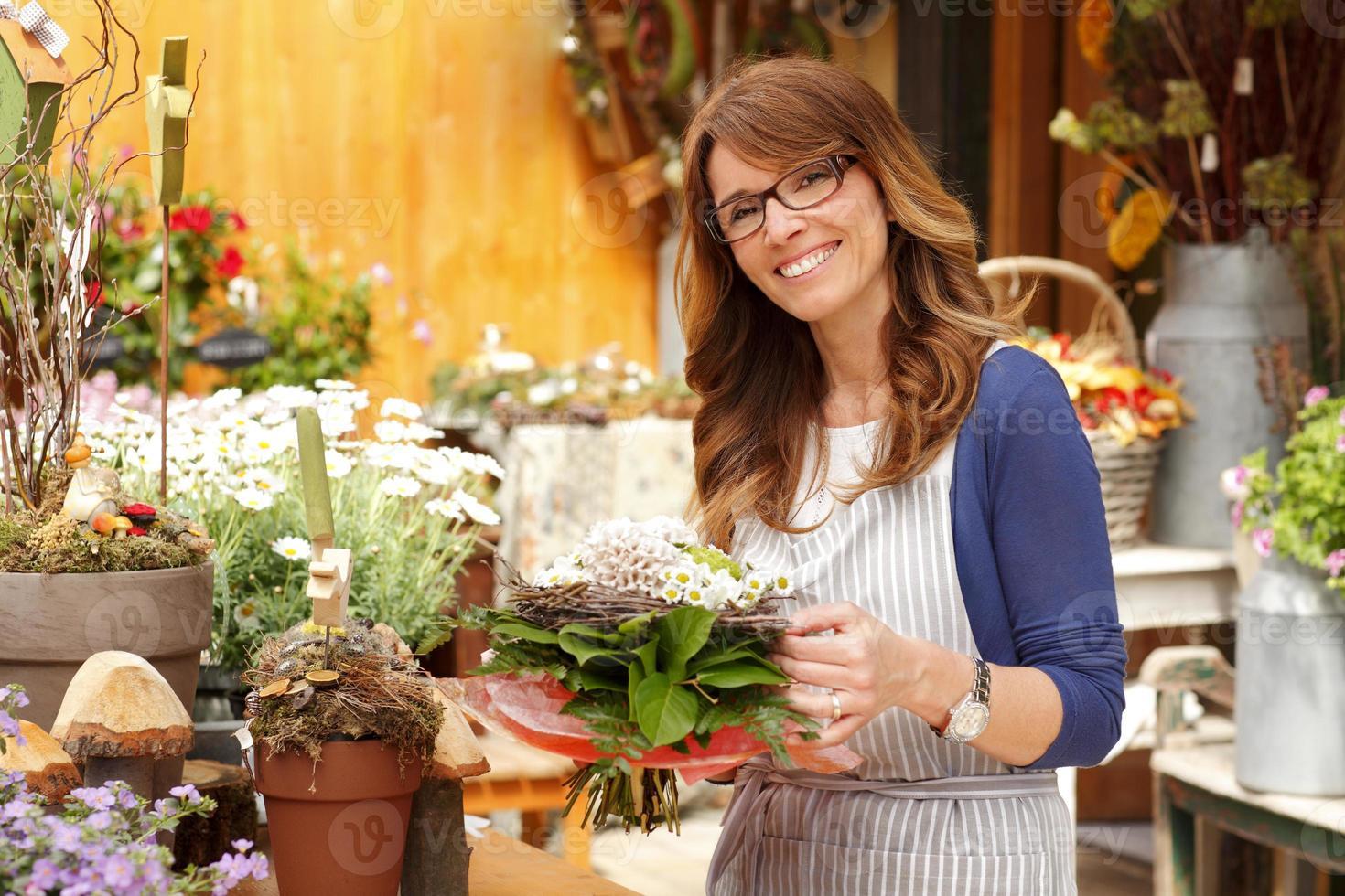 mulher de proprietário de loja de flores foto