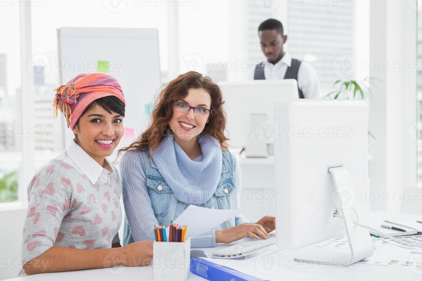 retrato do trabalho em equipe sorridente, sentado na mesa foto