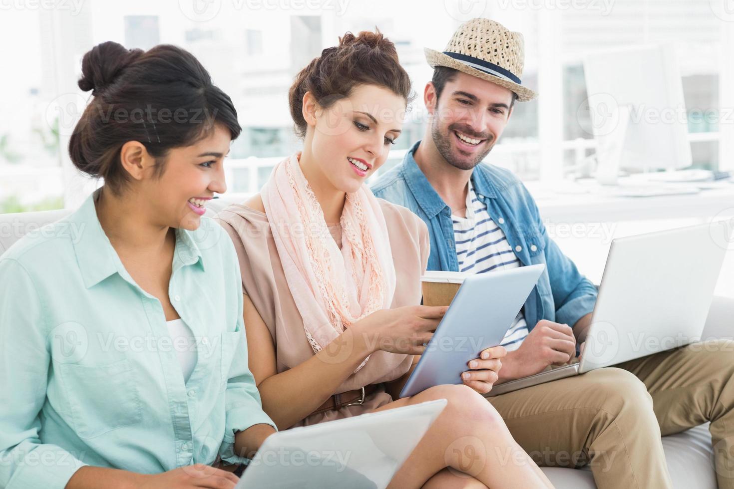 trabalho em equipe alegre usando laptop e tablet no sofá foto