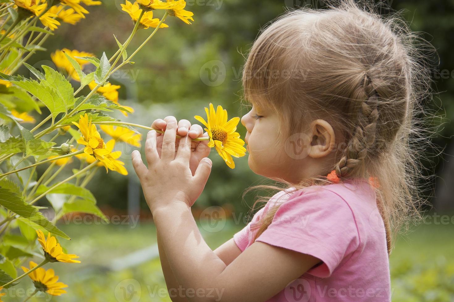 menina de três anos cheirando flor amarela foto