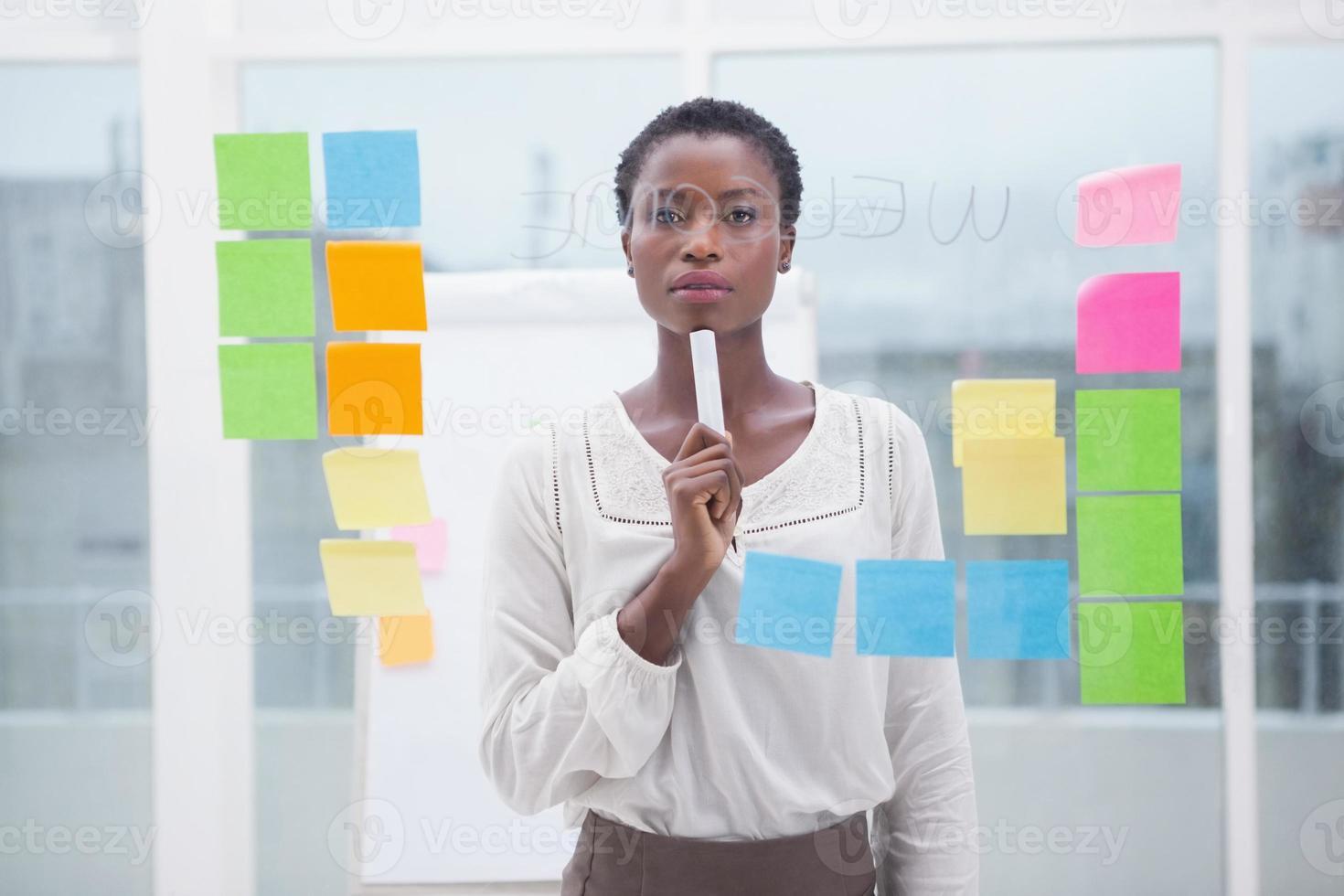 empresária pensativa, segurando um marcador foto