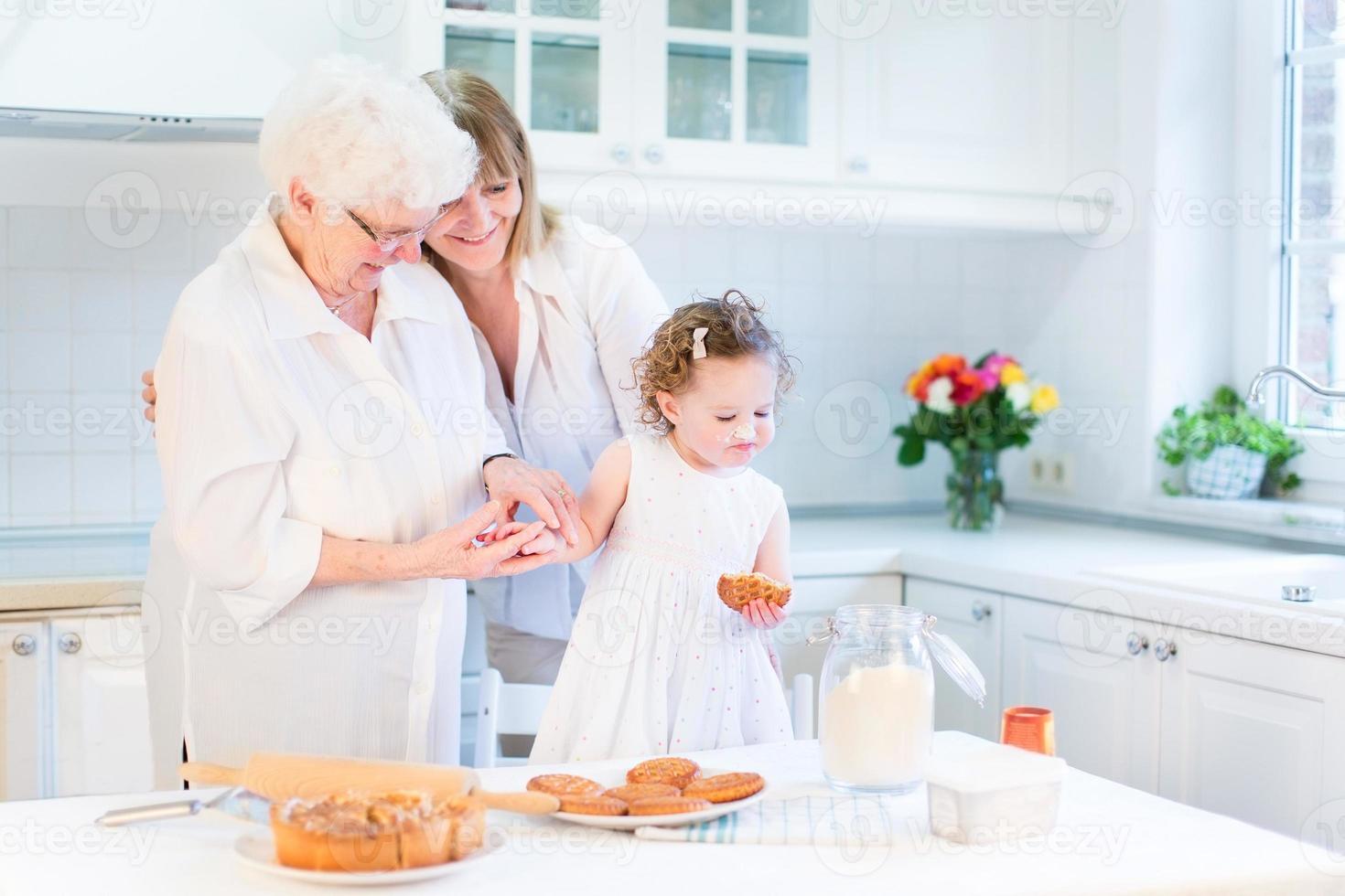 mulher feliz assando bolo com a mãe e filha criança sênior foto