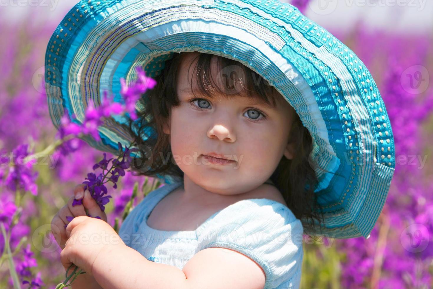 linda garota com grande chapéu azul sobre fundo natural foto