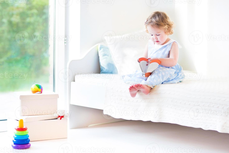 menina engraçada criança lendo livro sentado na grande janela foto
