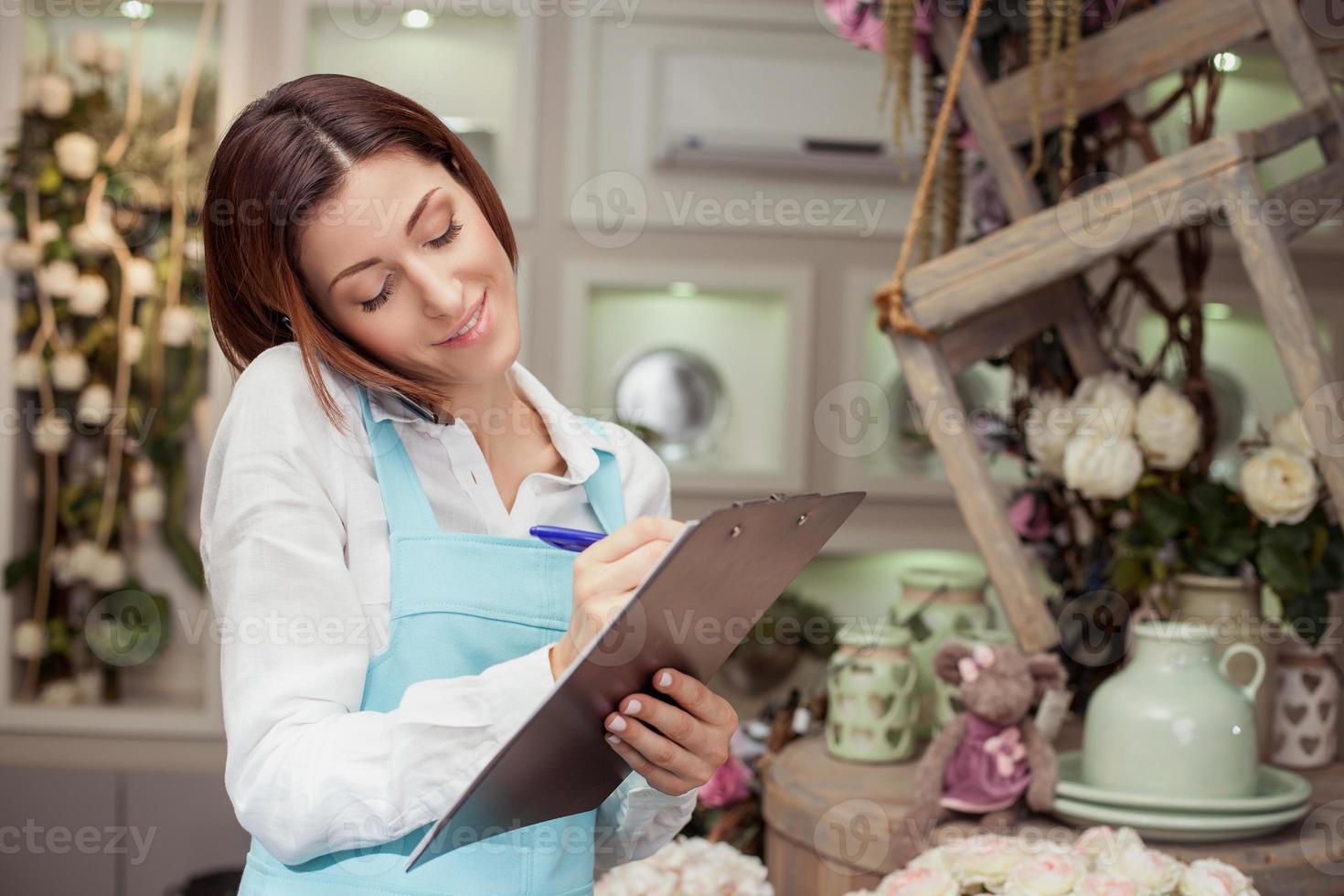atraente jovem vendedora está recebendo um pedido foto