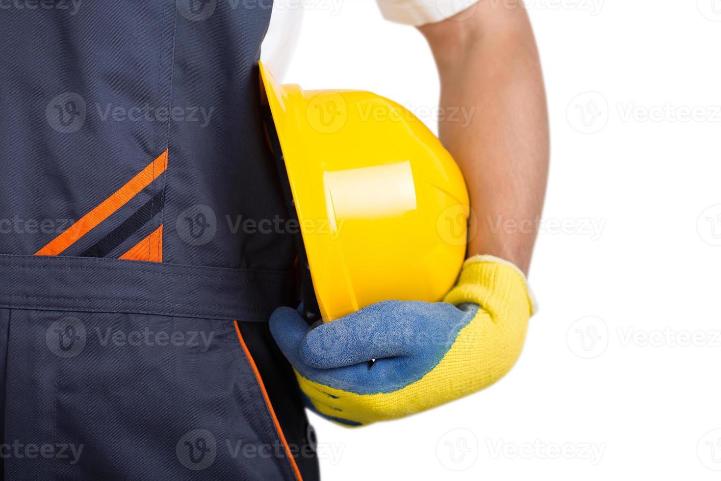 trabalhador segurando o capacete amarelo foto