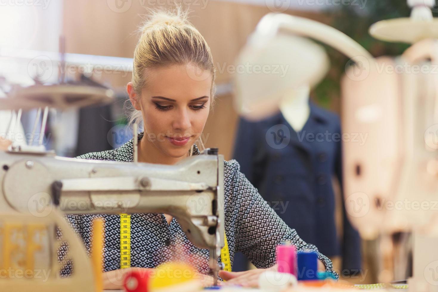 jovem mulher com máquina de costura foto