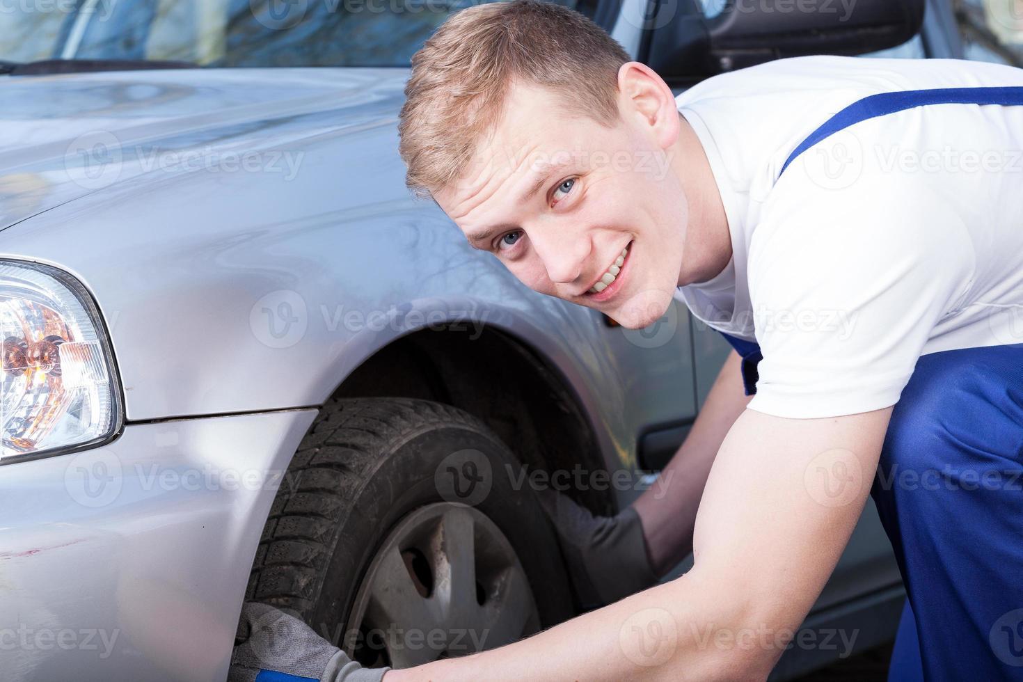mecânico de automóveis verifica um pneu de carro foto