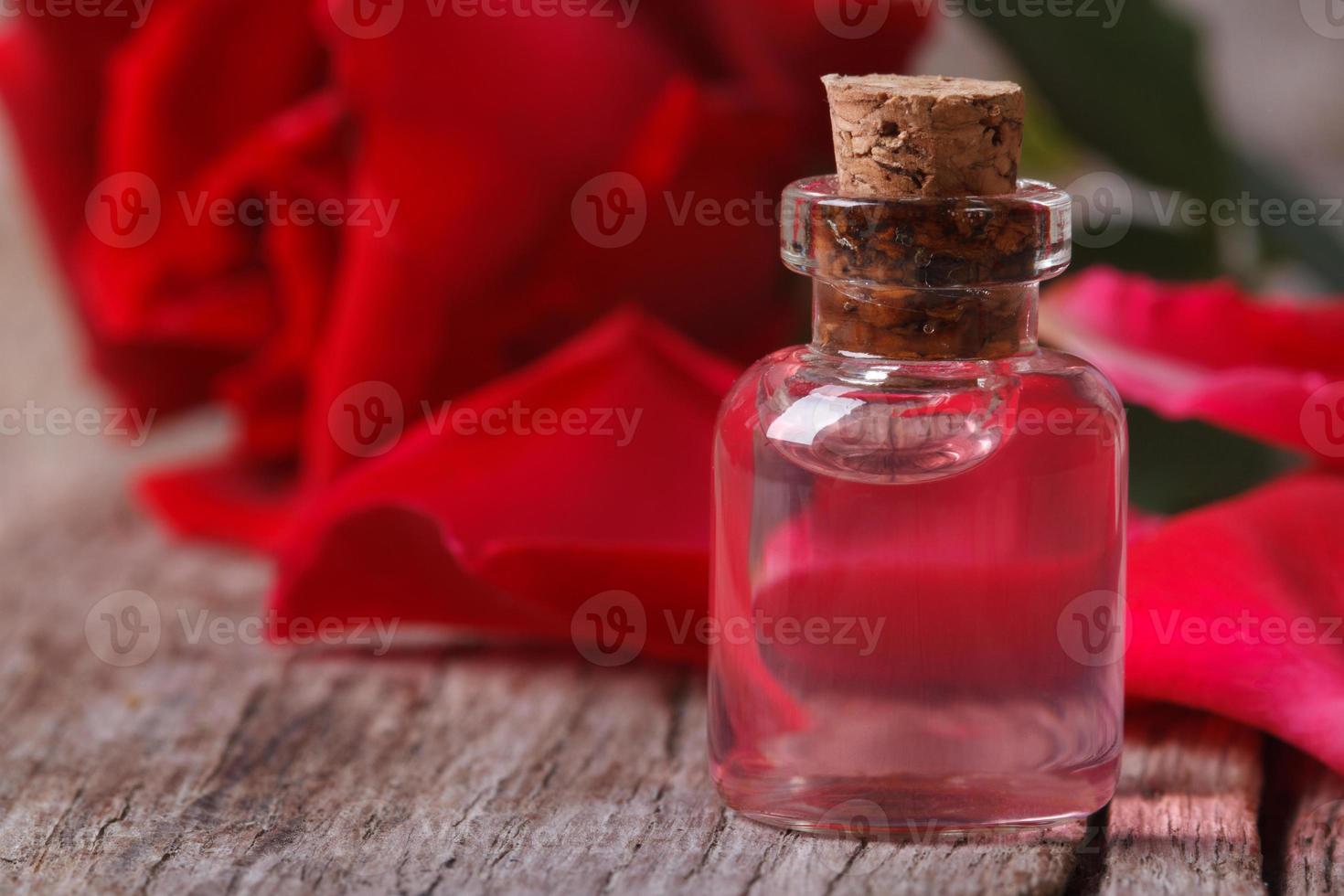 água de rosas perfumada em uma garrafa em um close de madeira foto
