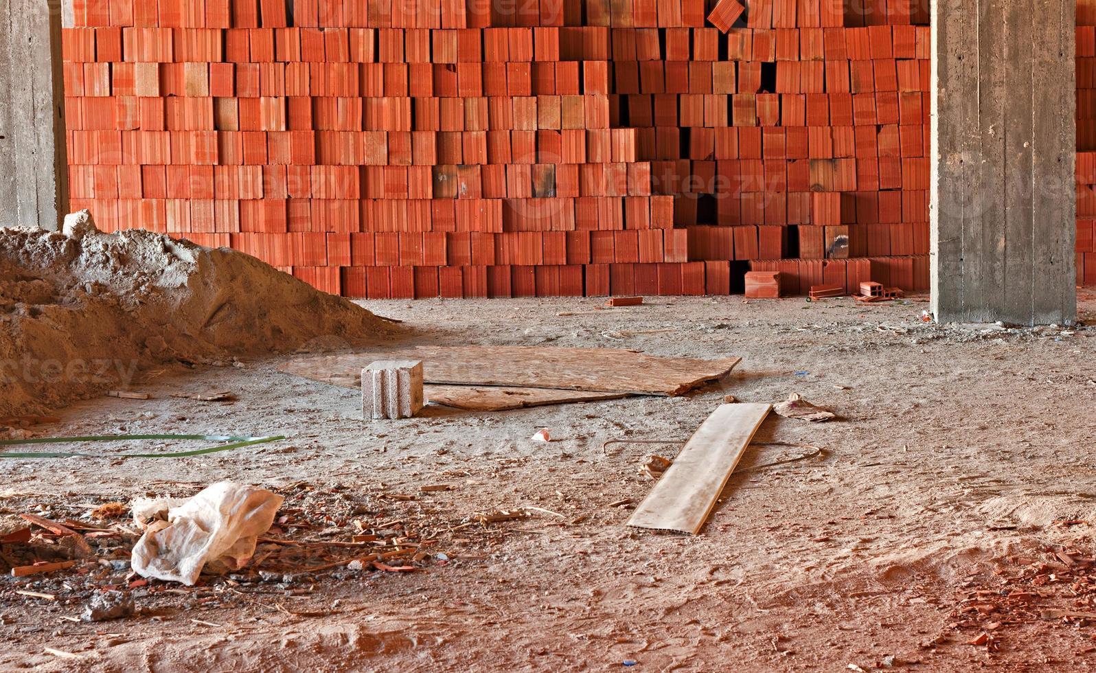 pilha de blocos de construção vermelhos dentro do canteiro de obras foto