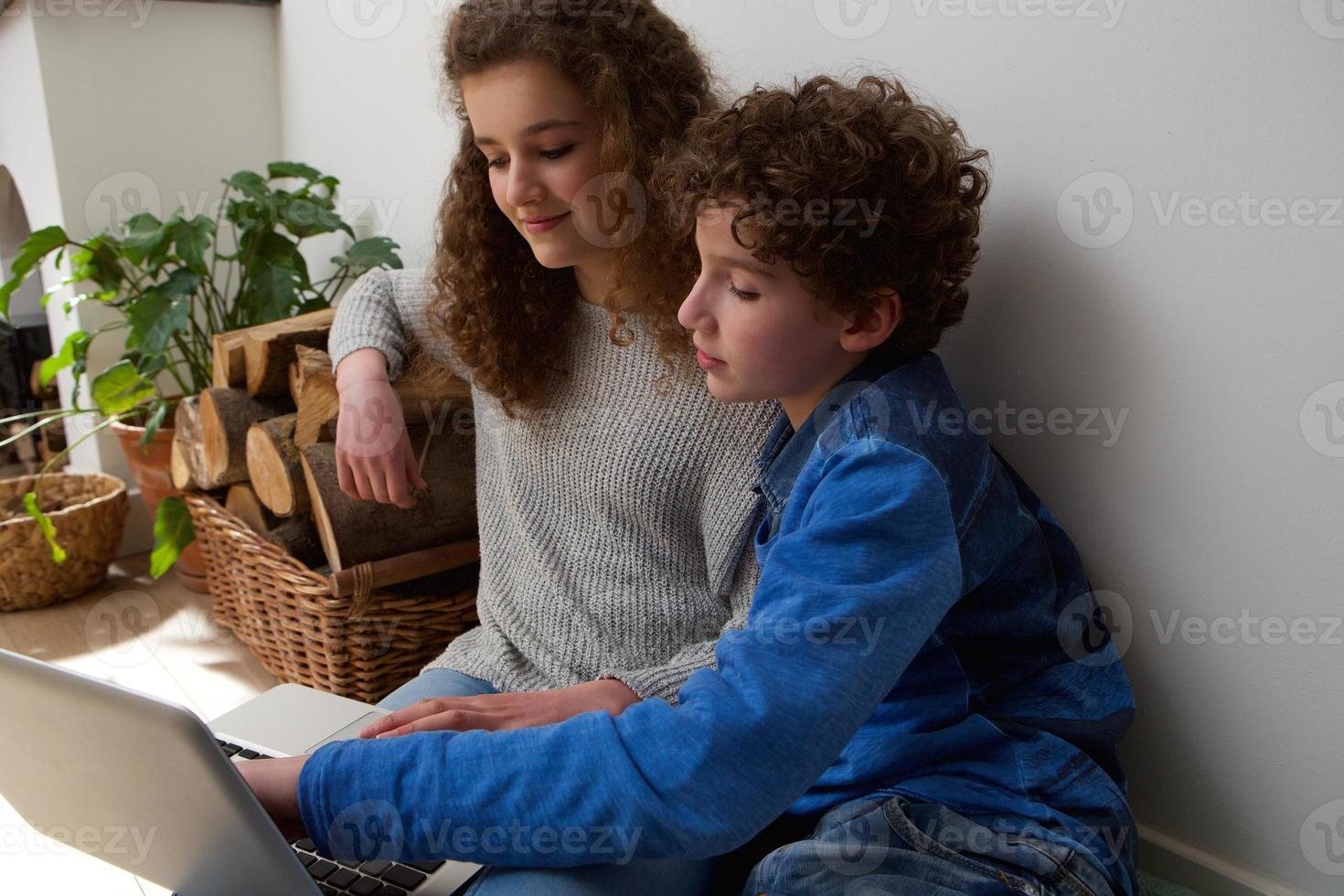 bonito menino e menina usando laptop juntos em casa foto