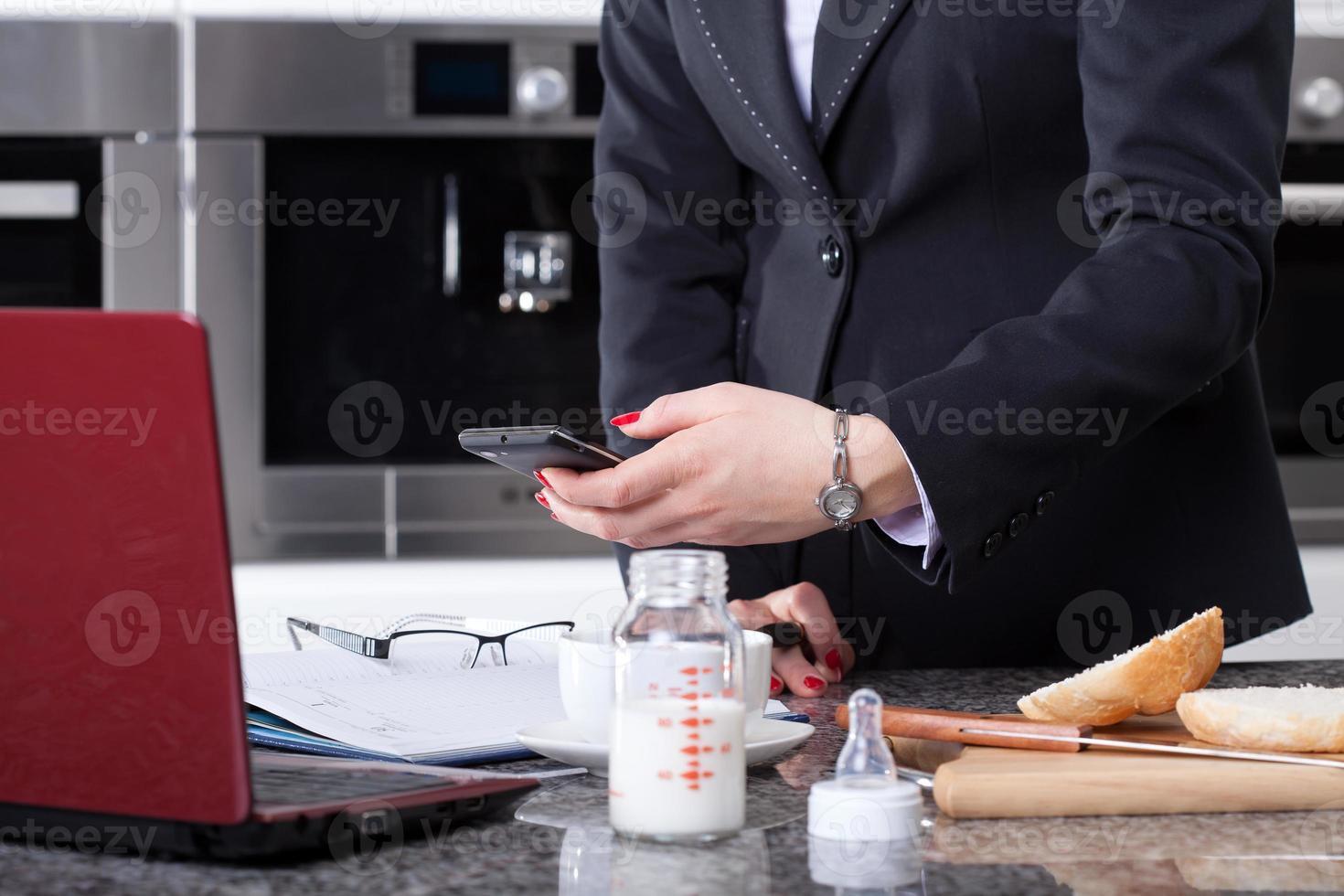 mulher moderna, preparando a refeição para criança e trabalhando de manhã foto