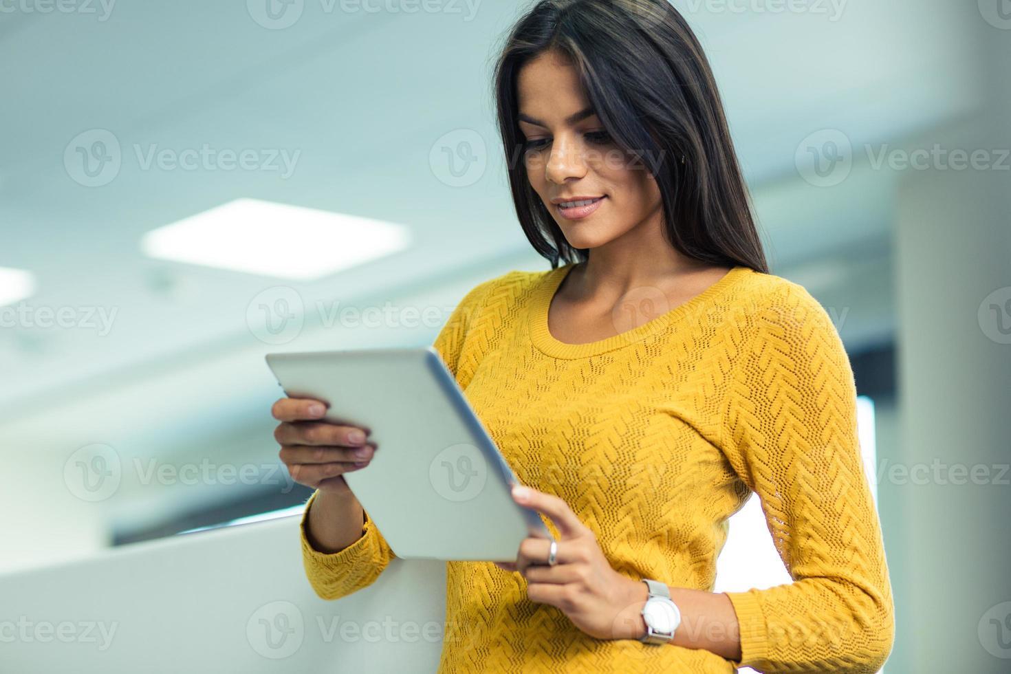 empresária usando computador tablet no escritório foto