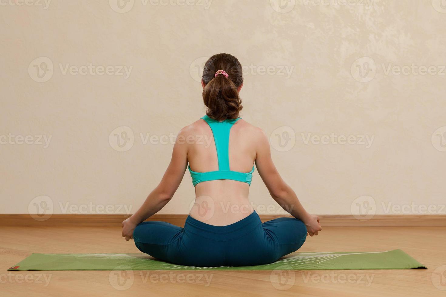 mulher caucasiana está praticando ioga no estúdio (sukkhasana) foto