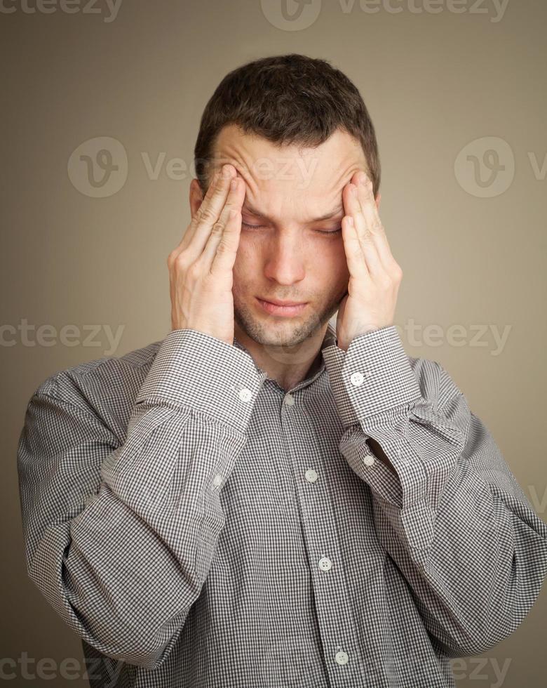 jovem homem caucasiano com dor de cabeça, retrato de estúdio casual foto