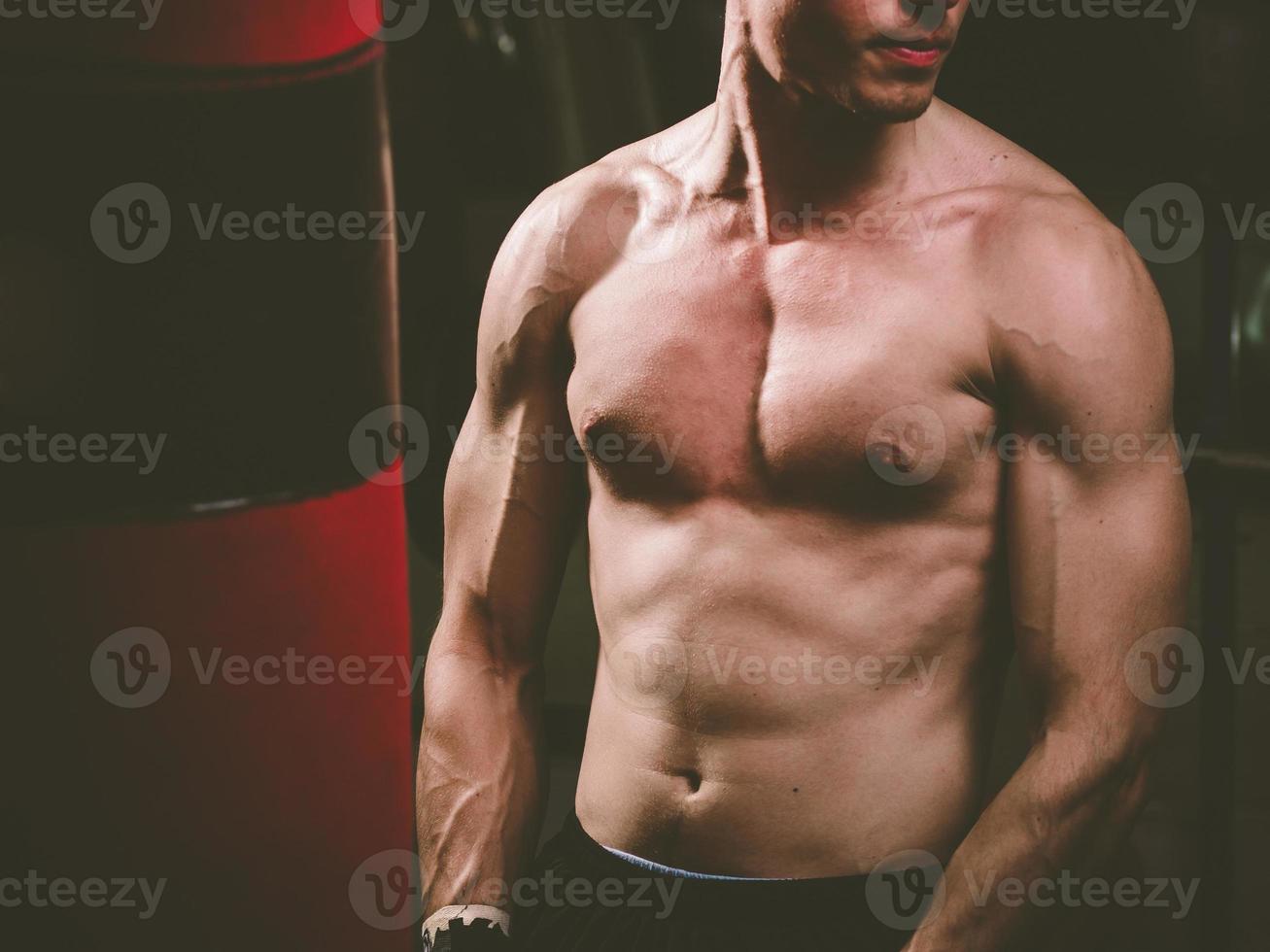 jovem boxeador caucasiano treinando com um saco de pancadas foto