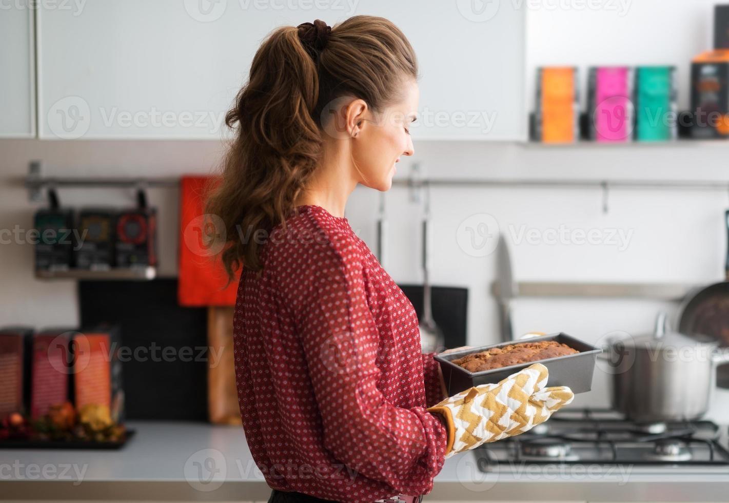 mulher em pé na cozinha, segurando a lata de pão quente foto