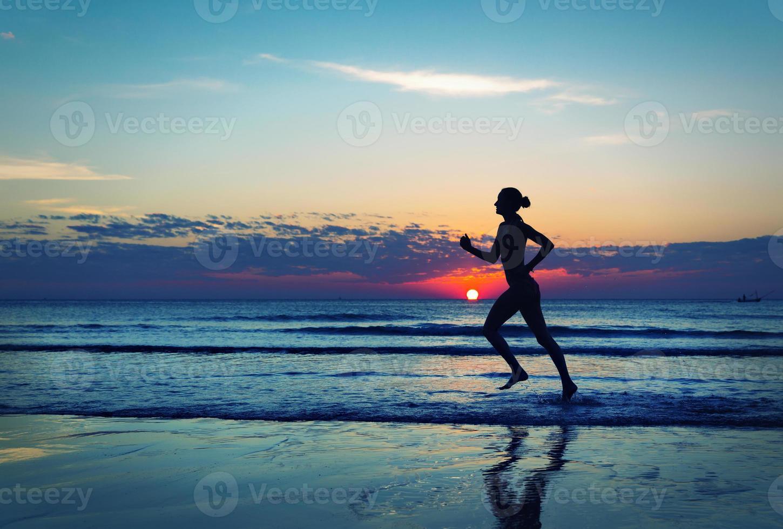 garota correndo ao longo da costa do mar foto