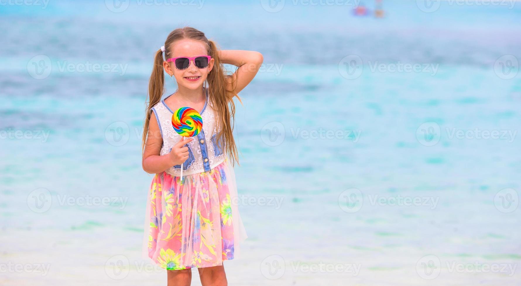 menina adorável se divertir com pirulito na praia foto