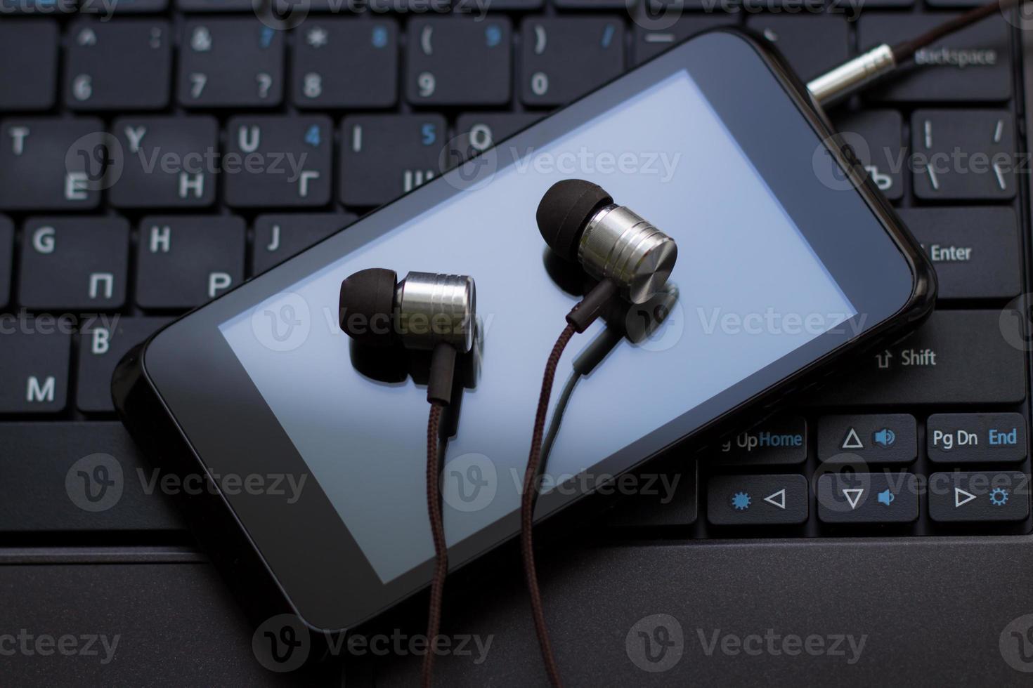 fones de ouvido e telefone celular no teclado. foto