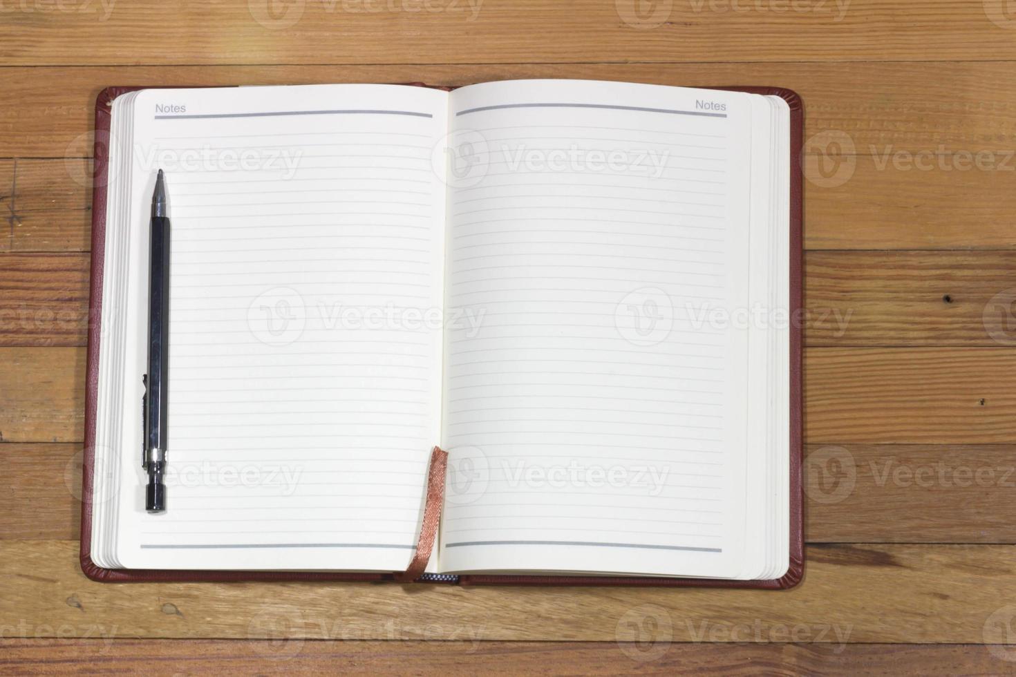 caderno em branco na mesa de madeira, conceito do negócio foto