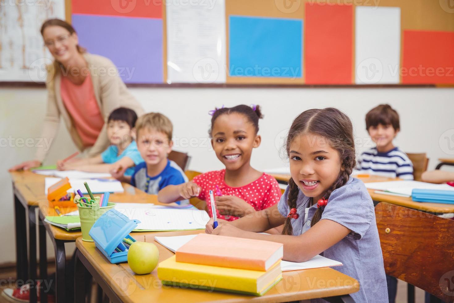 alunos bonitos desenho em suas mesas foto