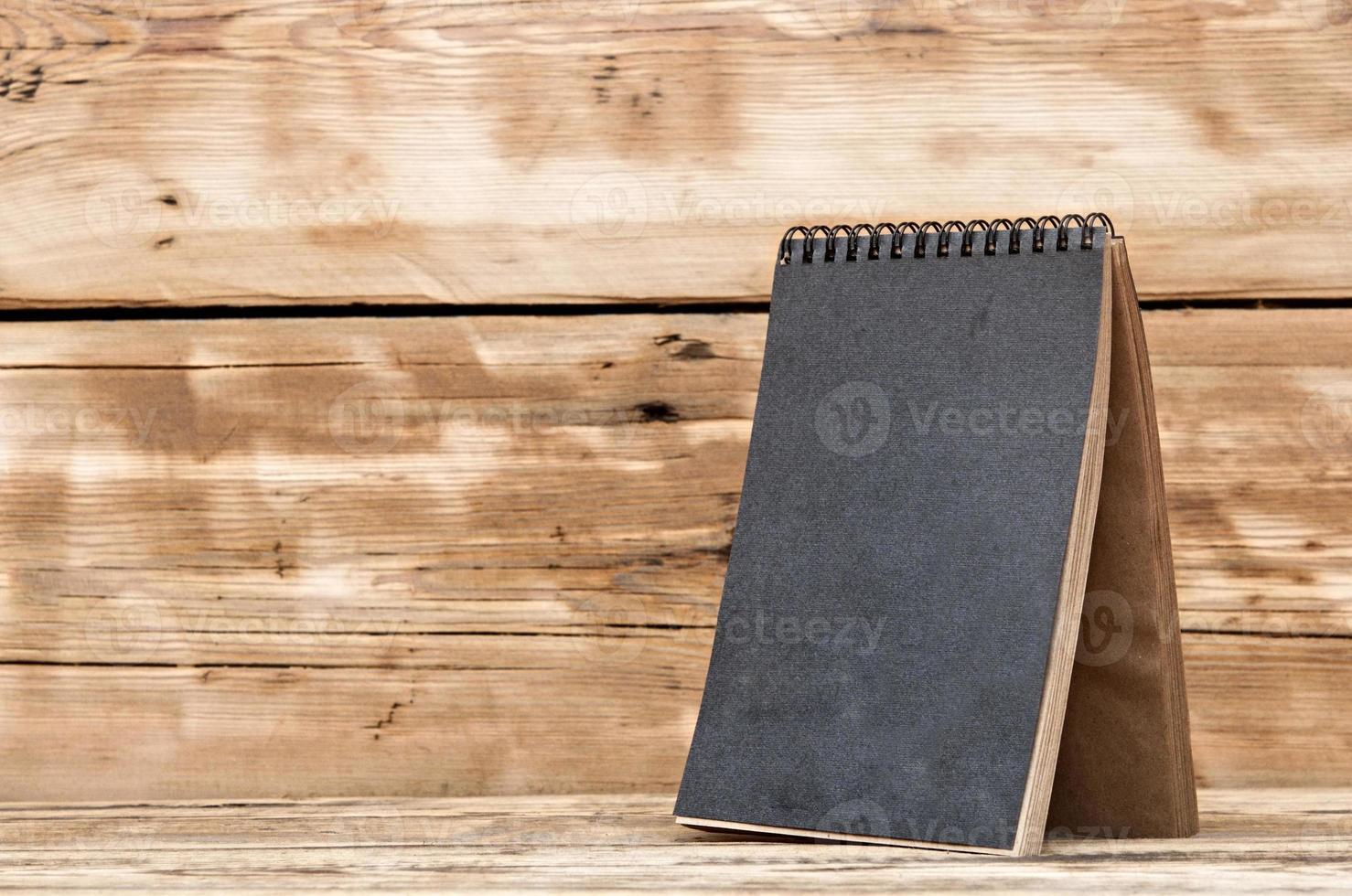 calendário de mesa em branco na mesa de madeira foto