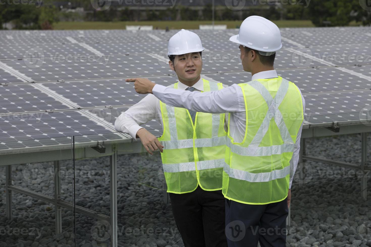 dois engenheiros asiáticos em uma estação de painel solar foto