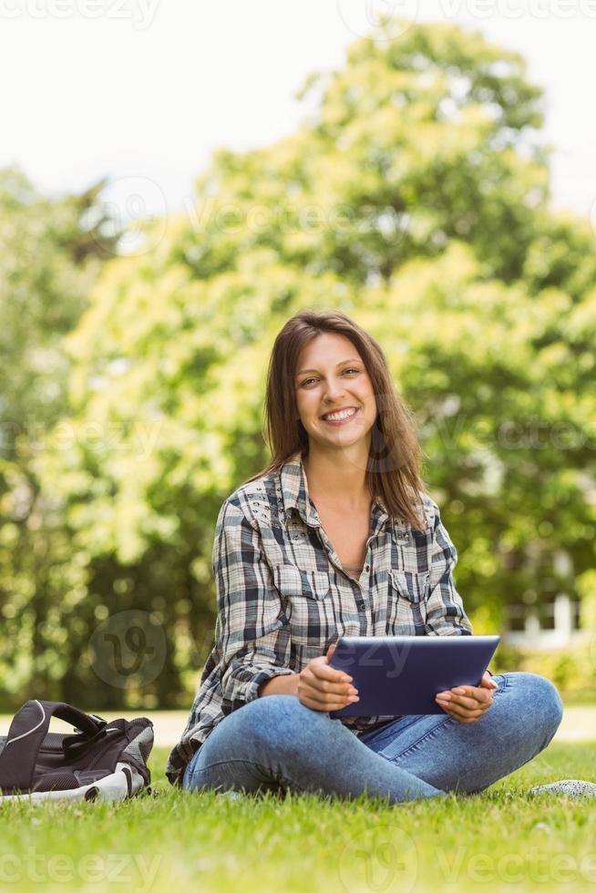 estudante sorridente, sentado e usando o tablet pc foto