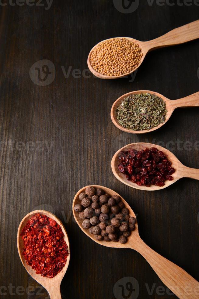 especiarias diferentes em colheres em fundo de madeira foto