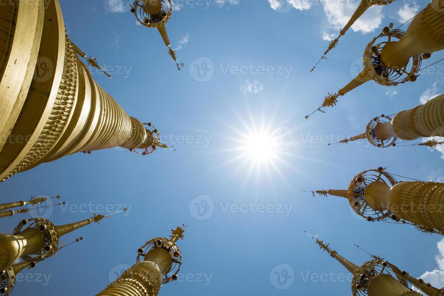 stupas de Mianmar dourado em um céu azul com sol foto