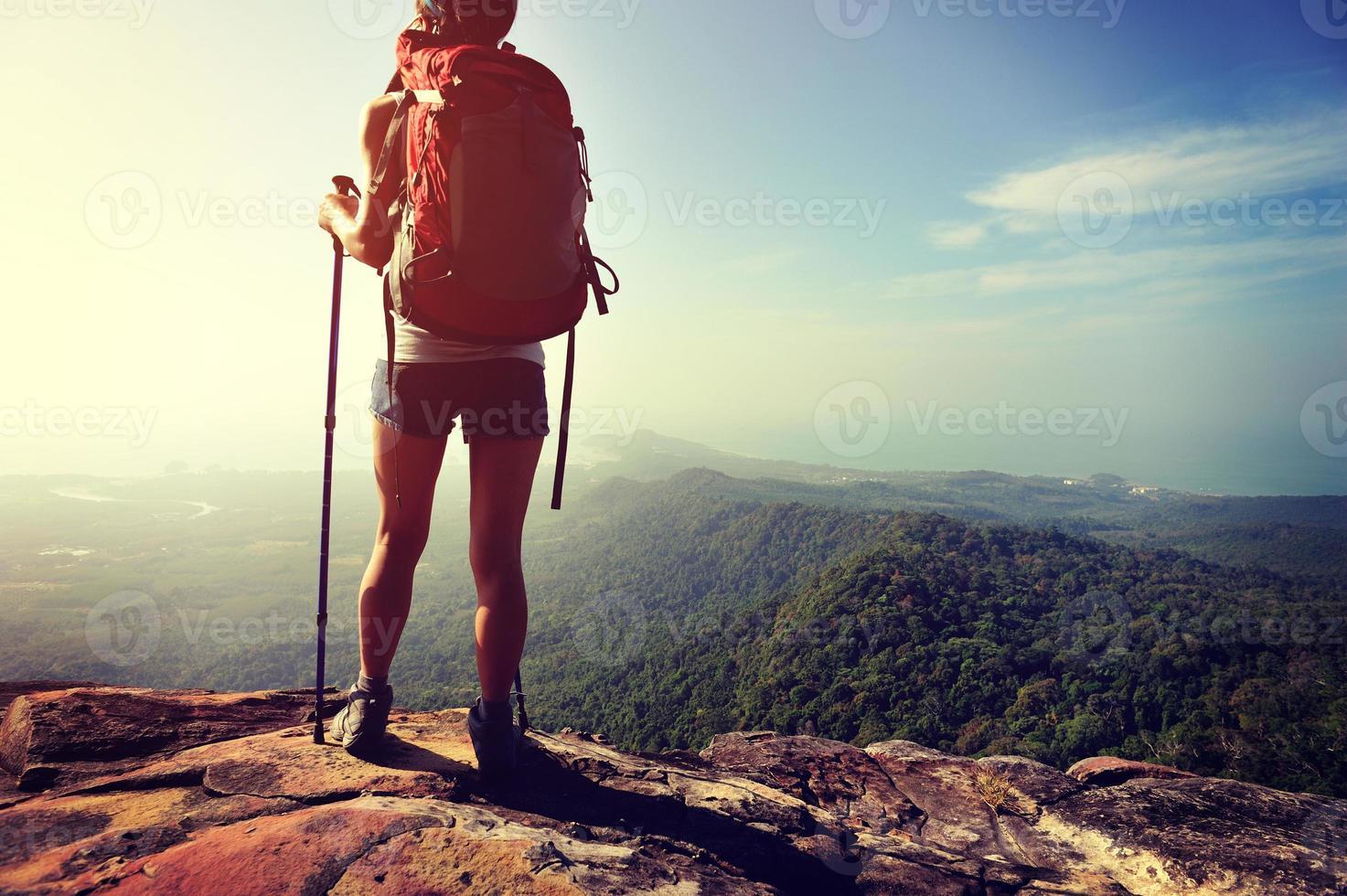 alpinista de mulher apreciar a vista no penhasco de pico de montanha foto