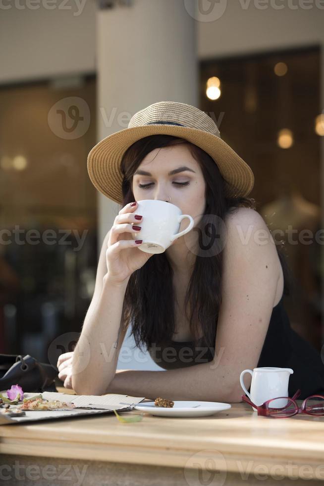 jovem viajante linda curtindo um café no café de rua foto
