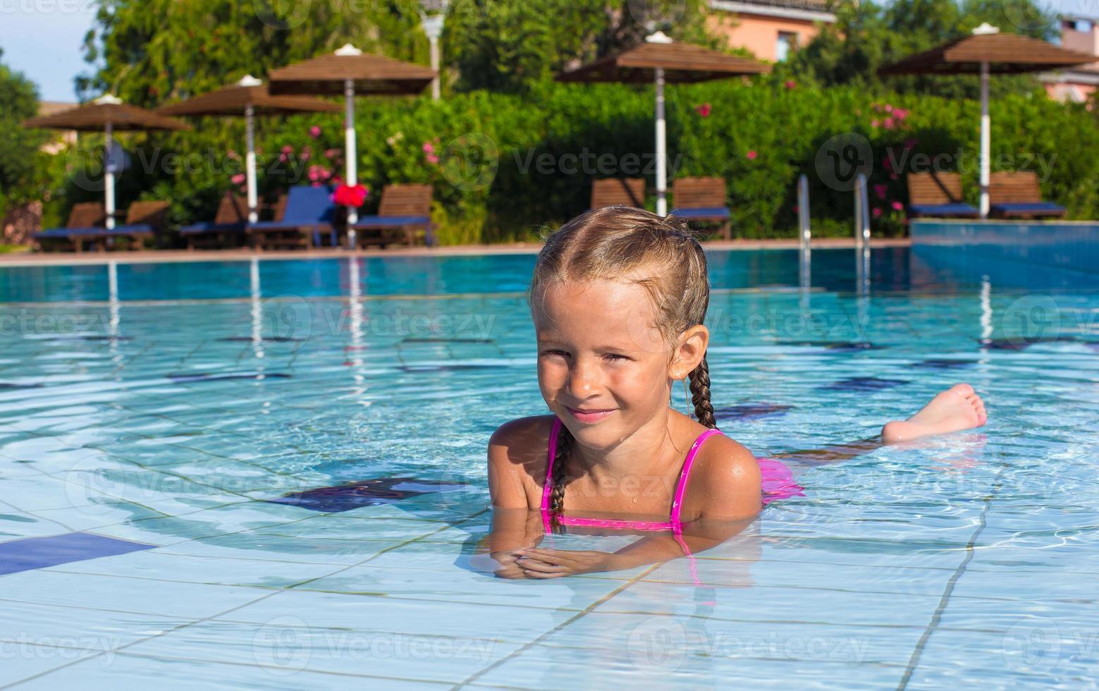 adorável menina feliz gosta de nadar na piscina foto