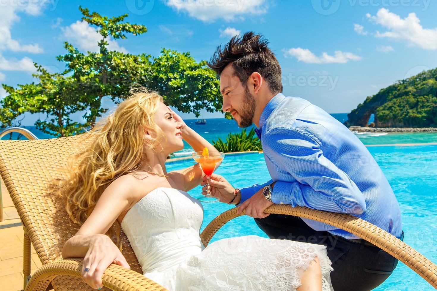 noiva e noivo felizes desfrutam de um infinito cocktail à beira da piscina foto
