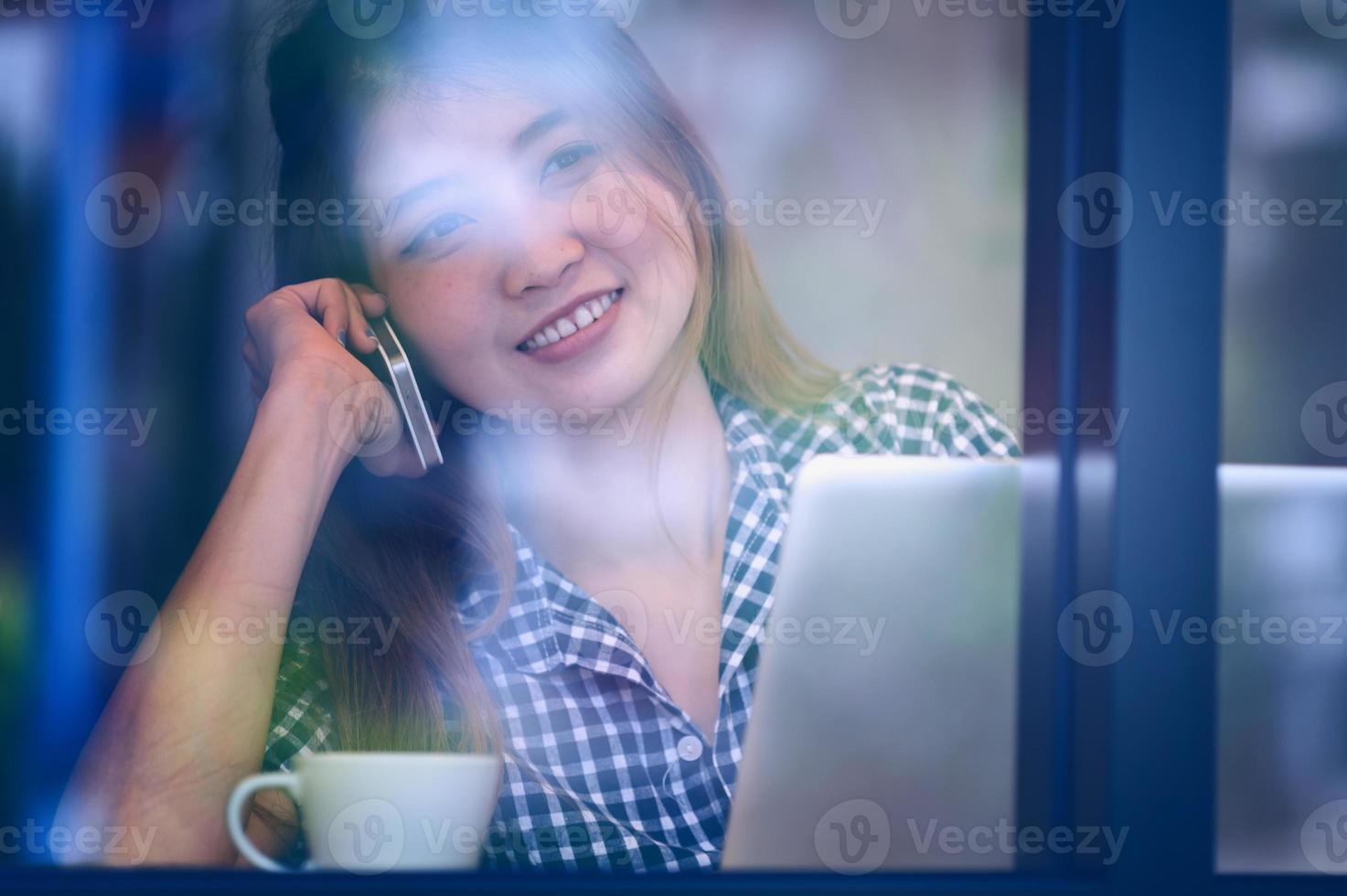 mulher feliz Ásia falando telefone no café e saborear café foto