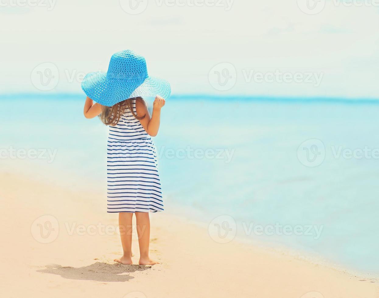 menina bonita no vestido e chapéu de palha, apreciando o mar foto