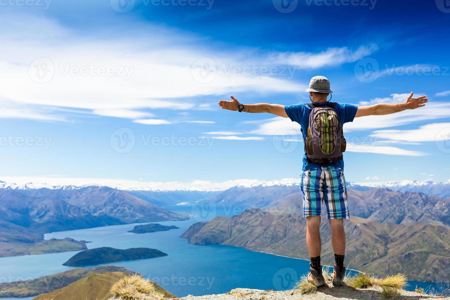 alpinista no topo de uma rocha, aproveite o dia ensolarado foto