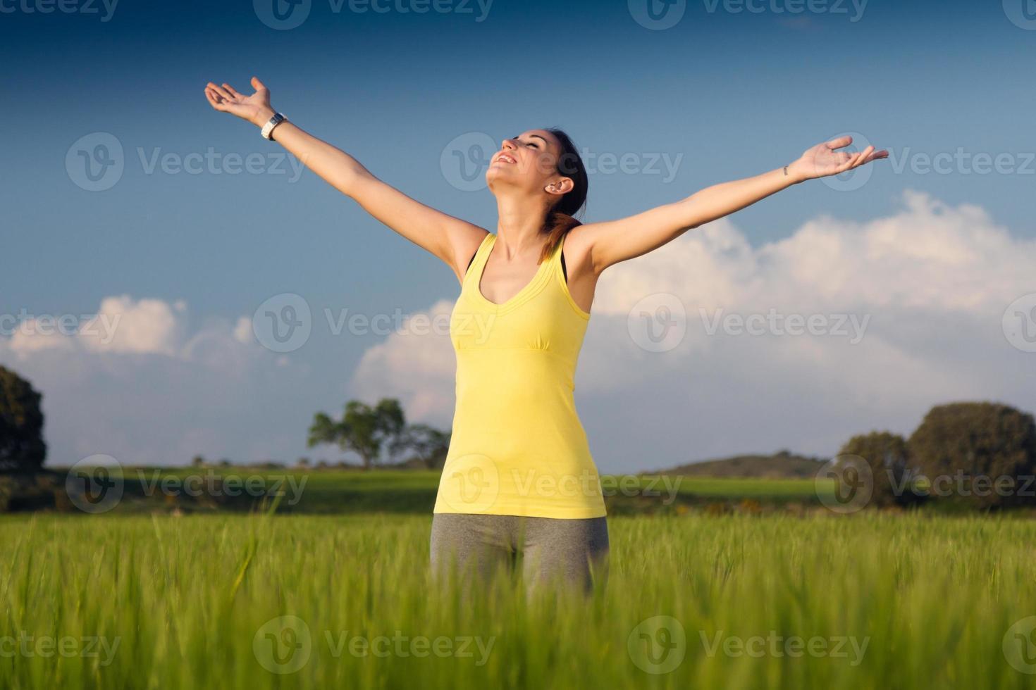 jovem desfrutando a primavera em pé em um campo de cereais foto