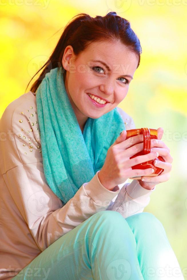 garota feliz relaxante no parque outono, desfrutando de bebida quente foto