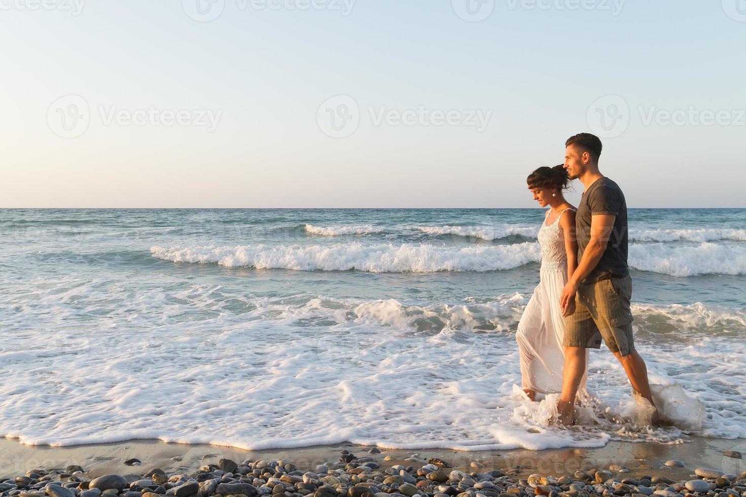 jovem casal gosta de andar em uma praia nebulosa ao entardecer foto
