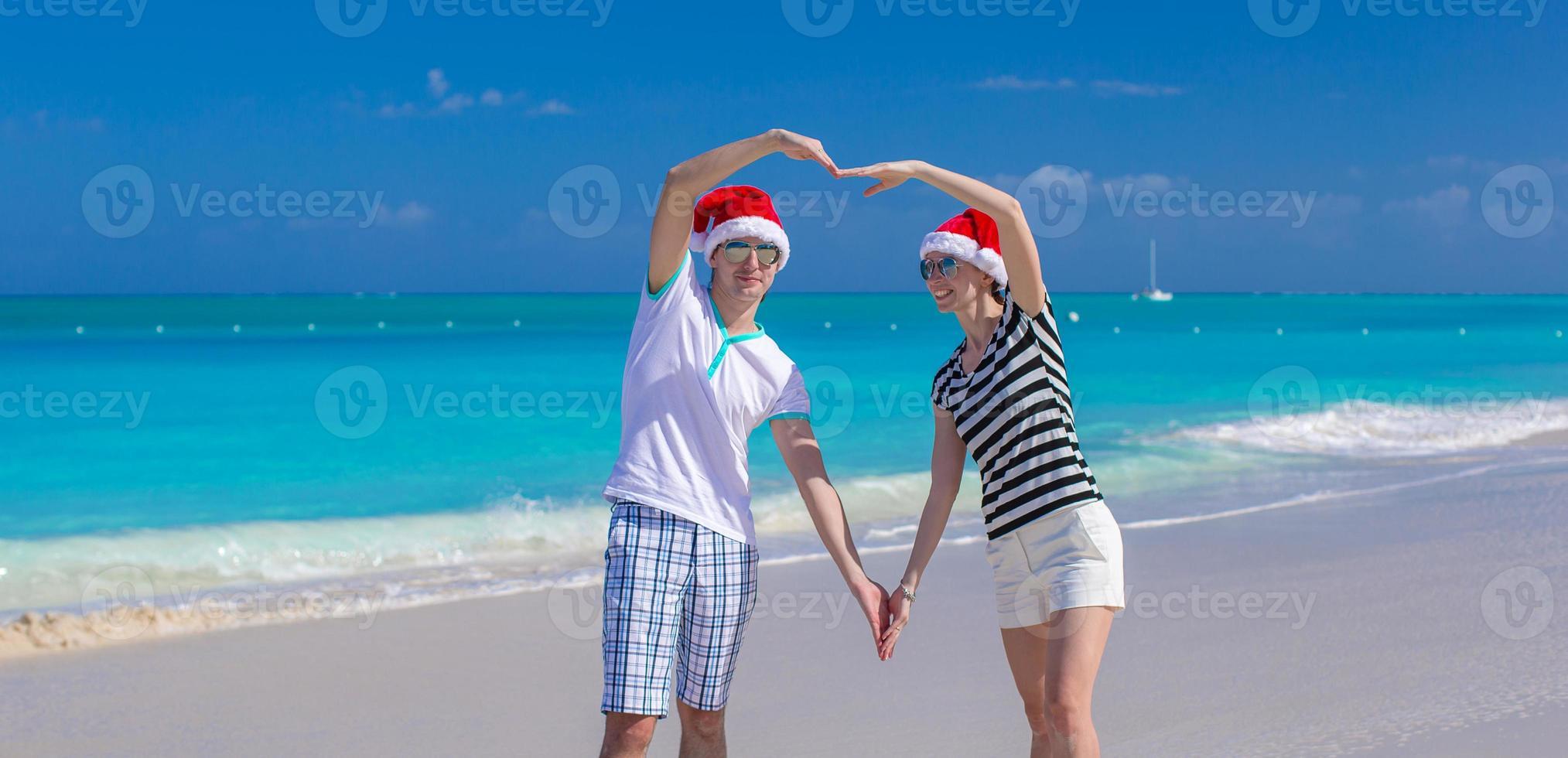 retrato de jovem casal de chapéu de Papai Noel curtir férias de praia foto