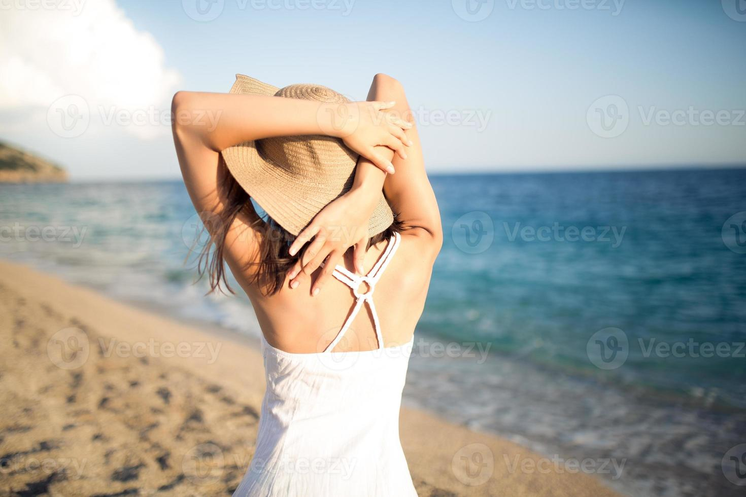 verão moda mulher desfrutando verão e sol, caminhando na praia foto