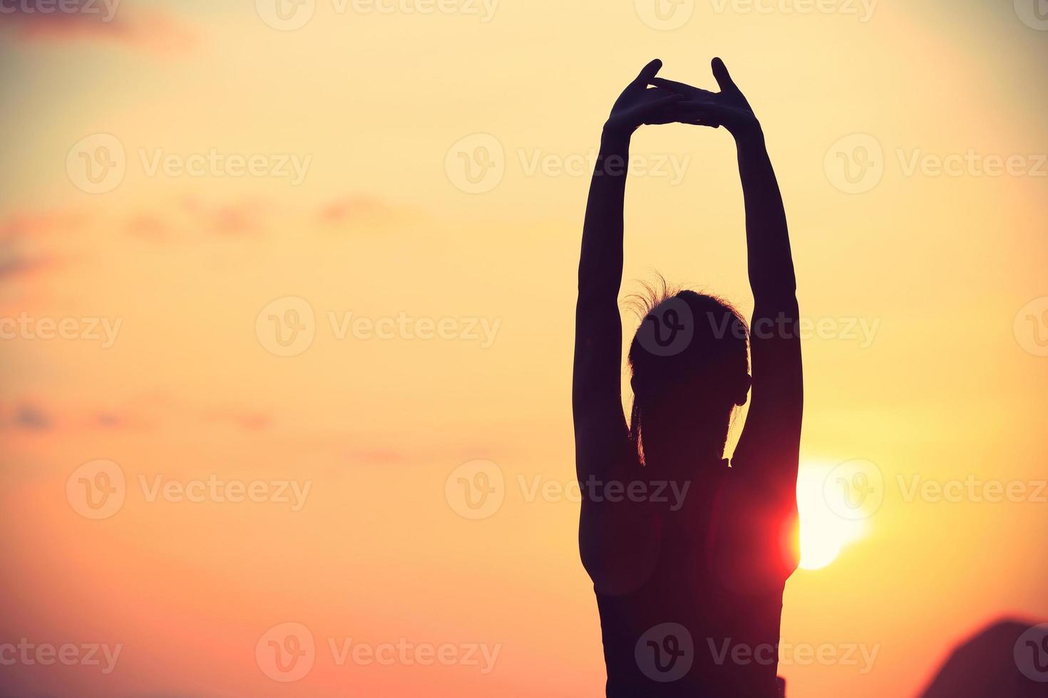 mulher de ioga fitness saudável, esticando os braços à beira-mar ao nascer do sol foto
