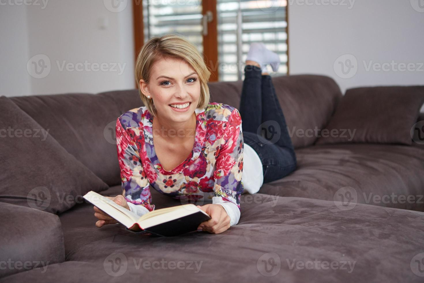 mulher que gosta de ler um livro em casa deitado no foto